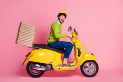 Profile side view of his he nice attractive crazy overjoyed cheerful cheery guy driving moped bringing pile stack pizza order punctuality isolated over pink pastel color background