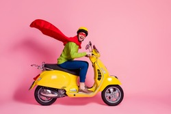 Profile side view of his he nice attractive crazy overjoyed cheerful cheery guy driving moped fast speed wearing cape rescue safe planet isolated over pink pastel color background