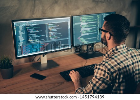 Profile side view of his he nice bearded guy wearing checked shirt professional expert html data base structure screen at wooden industrial interior work place station