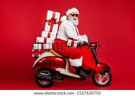 Profile side view of nice bearded cheerful fat funky Santa riding moped carrying pile stack fairy purchases shopping discount isolated on bright vivid shine vibrant red color background