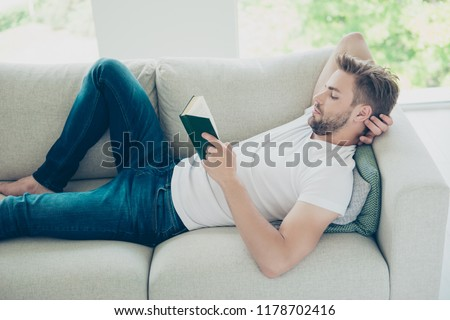 Profile side view photo of attractive, bearded, good-looking man in white t-shirt lying in bed, reader book after hard working week in light modern interior