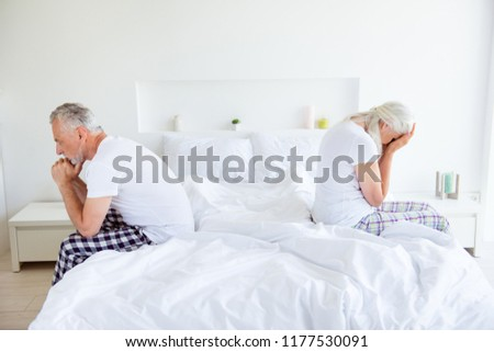 Profile side view photo of sad lovers after quarrel fight. Man and cry woman with gray hair sit back-to-back on the linen, sheets edge of the bed quarreled, did not talk