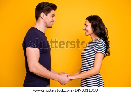 Profile side view portrait of his he her she nice attractive lovely tender affectionate cheerful cheery married spouses holding hands isolated on bright vivid shine yellow background