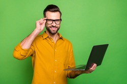 Profile side view portrait of his he nice attractive cheerful intellectual guy in formal shirt holding in hand laptop touching specs isolated on bright vivid shine vibrant green color background