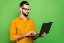 Profile side view portrait of his he nice attractive focused intelligent bearded guy in formal shirt holding in hands digital netbook isolated on bright vivid shine vibrant green color background