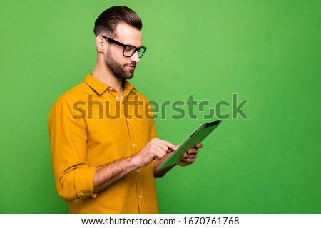 Profile side view portrait of nice attractive focused content guy in formal shirt holding in hand using digital tablet 5g connection isolated on bright vivid shine vibrant green color background
