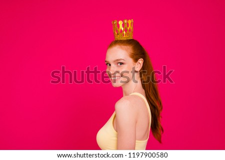 Profile side view portrait of nice cute attractive sweet lovely adorable cheerful positive optimistic pretty dreamy red-haired girl wearing golden crown, isolated on bright vivid fuchsia background