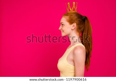 Profile side view portrait of nice cute attractive sweet lovely adorable cool cheerful positive glad red-haired girl wearing golden crown, isolated on bright vivid fuchsia background