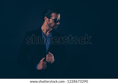 Profile side view portrait of nice cute lovely well-groomed content handsome attractive classy man in eyewear touching blazer suit isolated over dark black background #1228673290