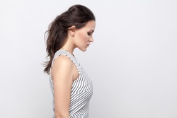 Profile side view portrait of sad beautiful young brunette woman with makeup and striped dress standing holding head down with hurt face. indoor studio shot, isolated on grey background.