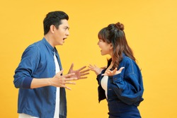 Profile side view portrait of two attractive angry aggressive nervous people having fight anger blame isolated over vivid shine bright orange background. Negative emotions concept.