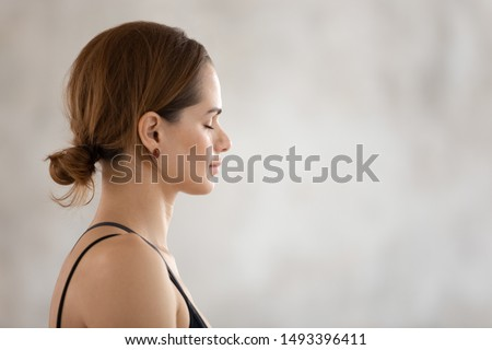Profile view beautiful woman with closed eyes practicing yoga, meditating, attractive girl wearing black sportswear relaxing, meditating in yoga studio or at home, stress relief close up