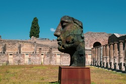 Profile view of a bronze face statue in the ruins of ancient Pompeii, Italy. Showing a thoughtful facial expression of the person portrayed. Testimony to a high culture, intellectuality and prosperity