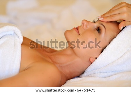 Profile view of a happy young woman preparing for cosmetic treatment