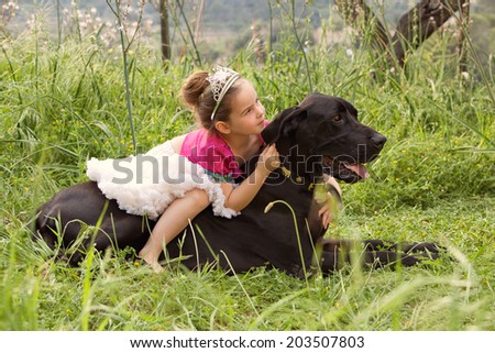 Profile view of a pretty young girl wearing a pink fancy dress, sitting on her dogs back enjoying a sunny holiday in a green park field, hugging him outdoors. Active family with pets, lifestyle.