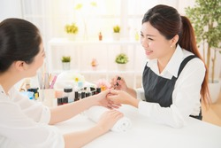 Profile view of a pretty young mixed asian women enjoy manicure and talking with her manicurist at real salon spa background. beauty and fashion concept.