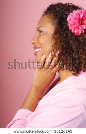 Profile view of a woman in a bathrobe at a spa on pink background
