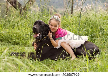 Profile view of a young girl wearing a pink fancy dress with crown, sitting on her dogs back enjoying a sunny holiday in a green park field, hugging and smiling. Active family with pets, lifestyle.