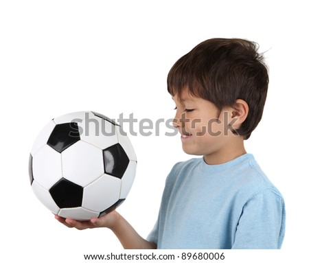 Profile view of a young happy boy holds a soccer ball  - on a white background