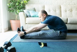Profile view of an active man in his 30s touching his toes and stretching out while following a yoga routine on his smartphone at home