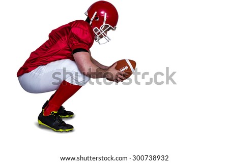 Profile view of an american football player in attack stance