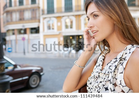 Profile view of an attractive businesswoman having a phone conversation in a classic city with traffic.