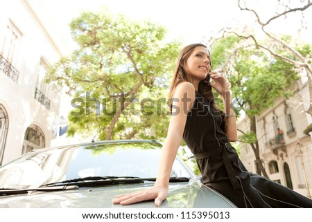 Profile view of an attractive businesswoman leaning on a car in a tree lined street, having a conversation with her cell phone.