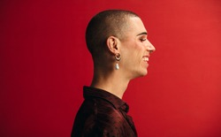Profile view of androgynous man wearing an earring and makeup smiling. Gay man smiling against red background.
