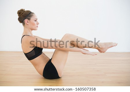 Profile view of beautiful woman doing a sports exercise in sports hall