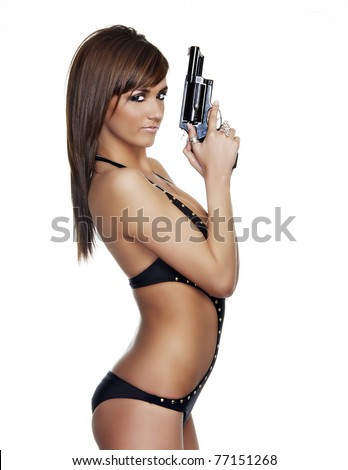 Profile view of beautiful young woman holding a pistol gun
