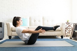 Profile view of fit young lady stretching and doing boat yoga pose in living room