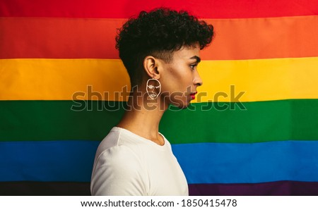 Profile view of gay man standing against pride flag. Transgender man wearing earring and makeup. Сток-фото ©