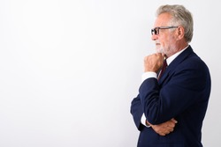 Profile view of handsome senior bearded businessman thinking while wearing eyeglasses against white background