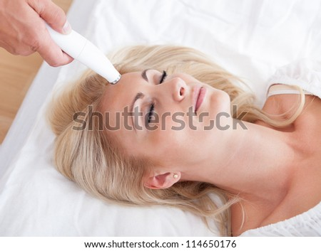 Profile View Of Happy Young Woman During Cosmetic Treatment, Indoors