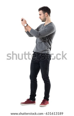 Profile view of serious young casual man holding cellphone taking photo. Full body length portrait isolated over white studio background.