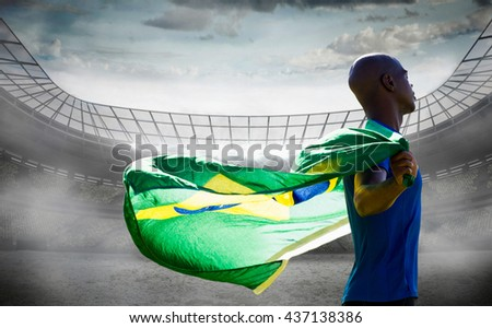 Profile view of sportsman holding a Brazilian flag against stadium #437138386
