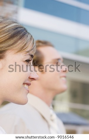 profile view of two businesspeople standing side by side looking straight smiling
