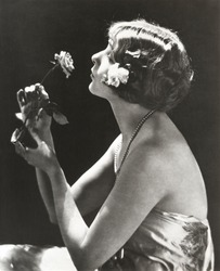 Profile view of young woman smelling flower