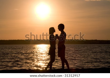 Profiles of romantic couple looking at each other on background of lake at sunset