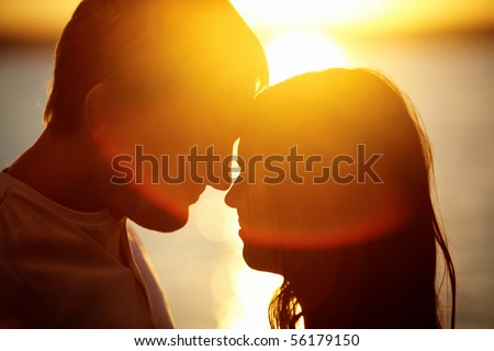 Profiles of romantic couple looking at each other on background of sunset