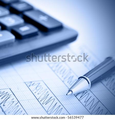Profit bar chart, pen and calculator. Shallow DOF! Focus on the pen.