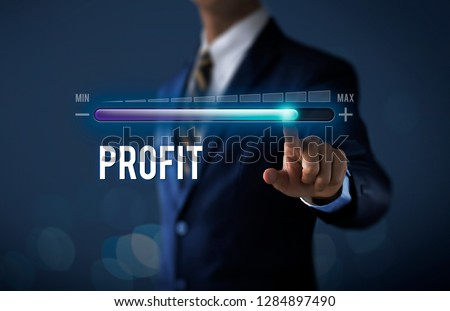 Profit growth, increase profit, raise profit or business growth concept. Businessman is pulling up progress bar with the word PROFIT on dark tone background. #1284897490