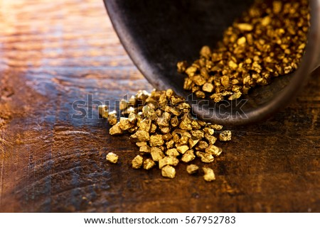 Profit, trade and exchange. Gold nuggets spilling out from a grungy old metal container, placed on a old wooden table.Shallow depth of field.