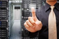 Programmer in data center room press on power button