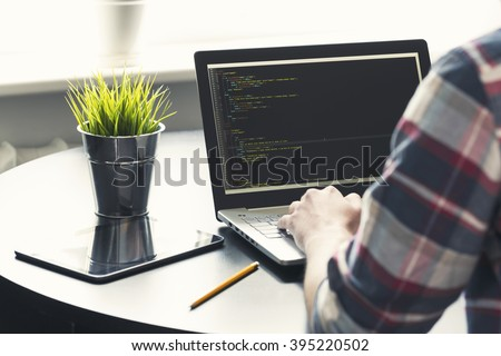 programmer working on laptop at office. focus on programming code