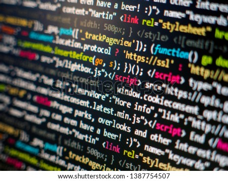 Programming code on black background. It is HTML and javascript code with highlighted scripts and functions. Script on computer with source code – screen of software developer. Javascript code.
