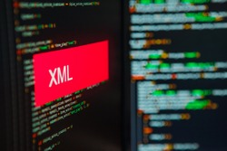 Programming language, XML inscription on the background of computer code. Modern digital technologies and programming training