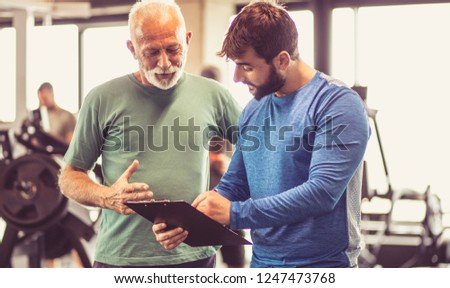 Progress is visible. Personal trainer giving advice senior man about next exercise. Close up.