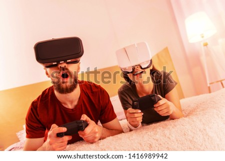 Progress. Progressive couple having fun while playing virtual reality at home #1416989942