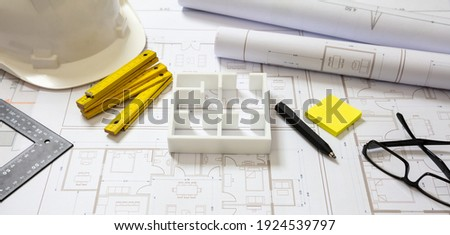Project blueprints, house model and engineer hardhat white color, Housing project construction, architect site office background. ストックフォト ©